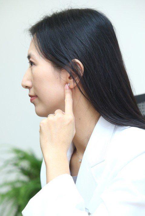 中醫師羅珮琳臉部按摩聽會穴,聽會穴會在張嘴時空凹。記者曾學仁/攝影