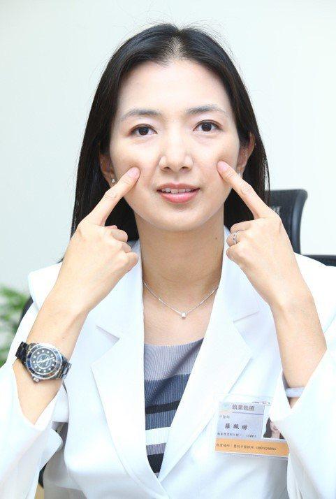 中醫師羅珮琳示範按摩巨髎穴,位在鼻下與瞳孔直下交接處,有助拉提臉部肌肉,促進氣血...