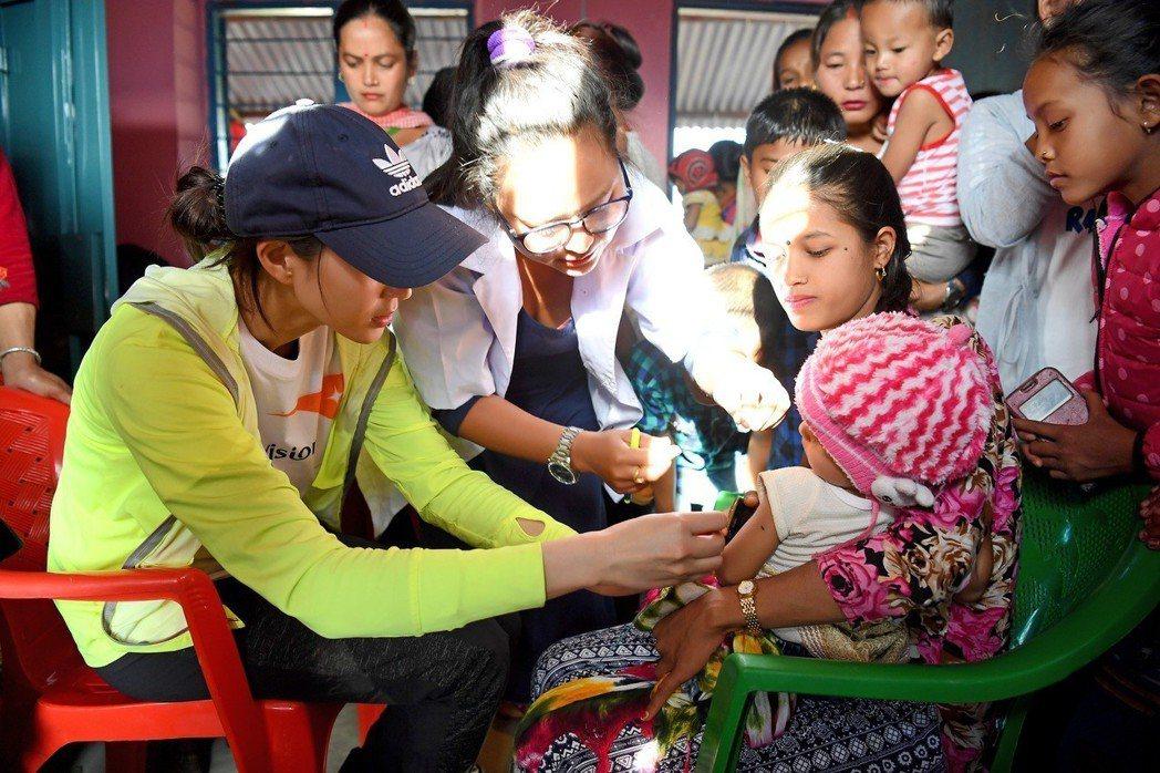 張鈞甯在基礎保健站幫小朋友測量是否有營養不良問題。圖/世界展望會提供