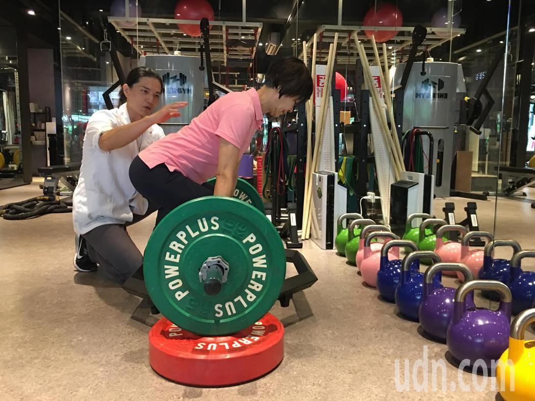 66歲張女士(右)因骨質疏鬆及肌力流失,過去體重僅42公斤,在物理治療師郭仕政(...