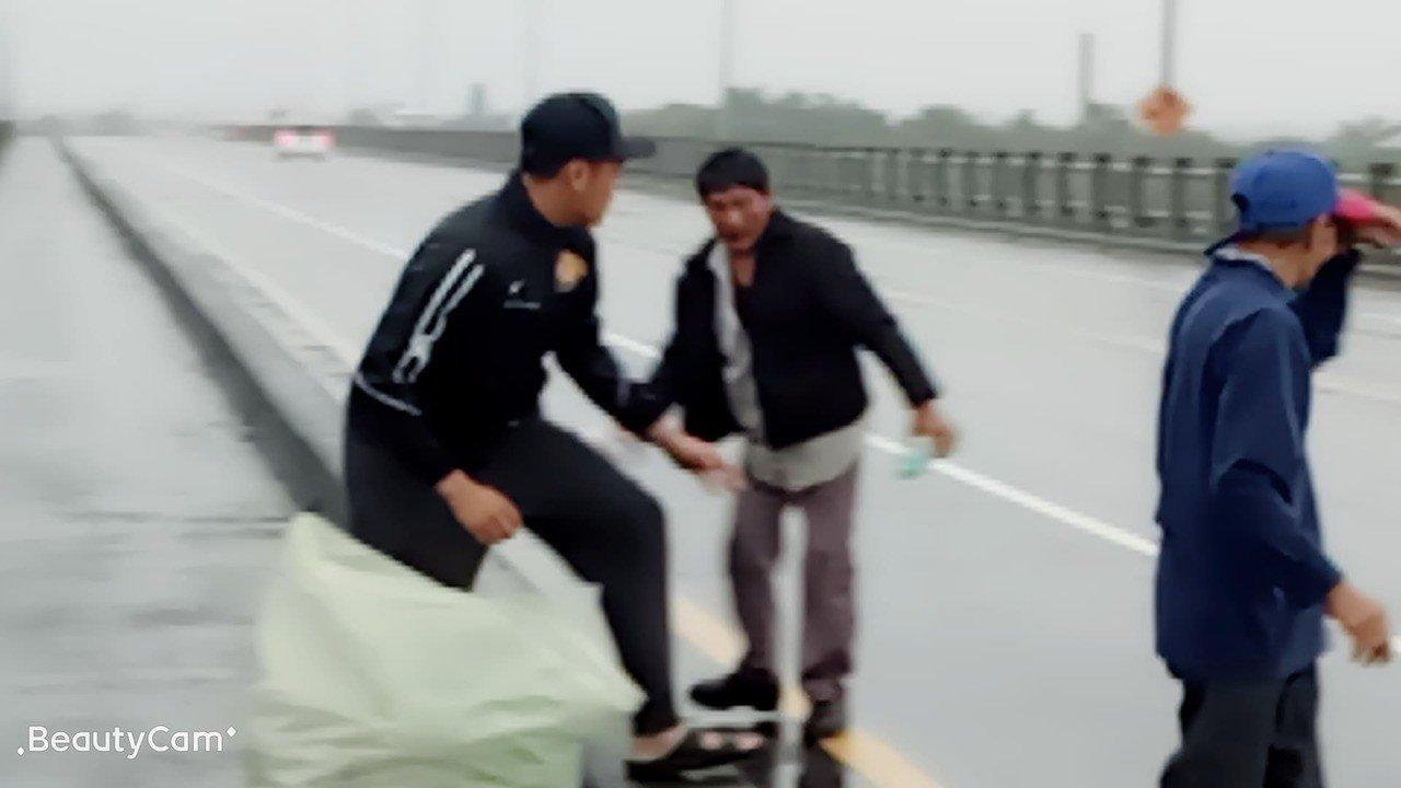 董子浩(左)協助兩名老翁撿拾散落橋上的空寶特瓶。圖/民眾提供