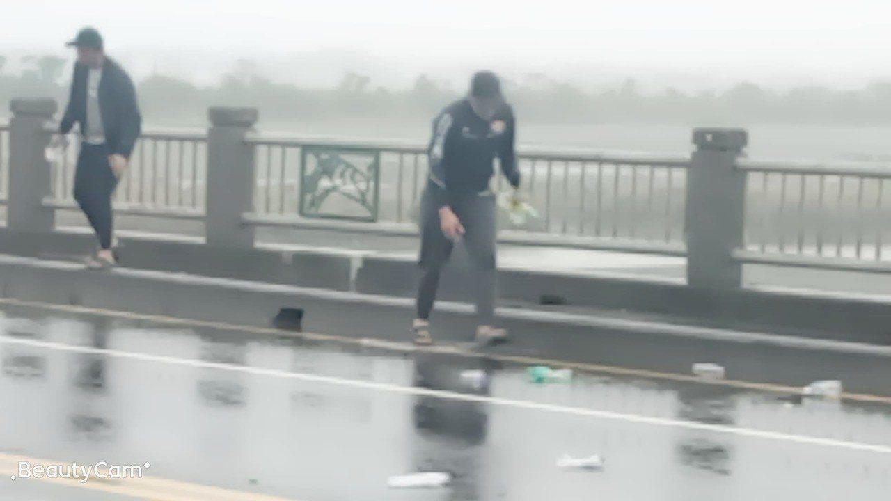 岳東華(左)、董子浩(右)協助撿拾散落橋上的空寶特瓶。圖/民眾提供