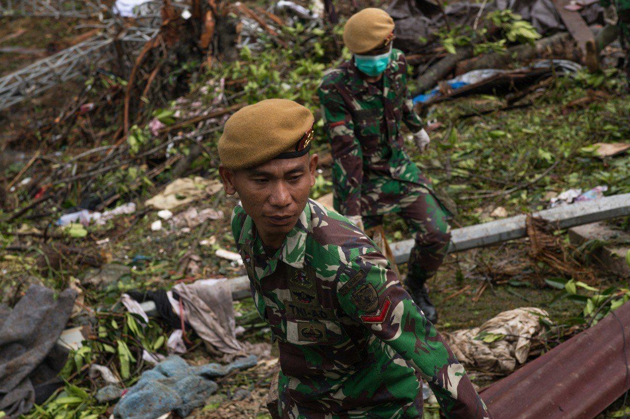 印尼軍方與搜救隊24日冒雨搜尋海嘯生還者。 新華社