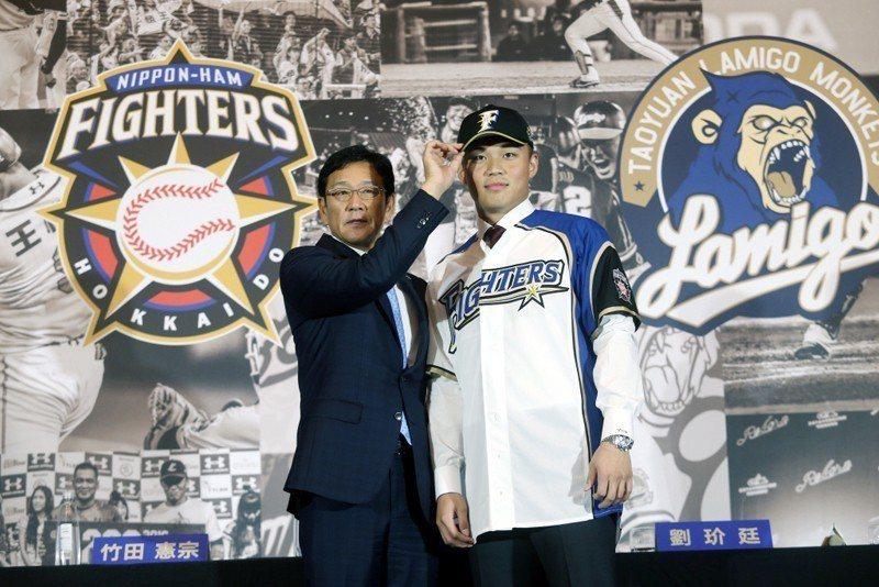 19日在台灣的加盟記者會上,火腿隊總教練栗山英樹為王柏融戴上火腿球帽。 圖/聯合報系資料照