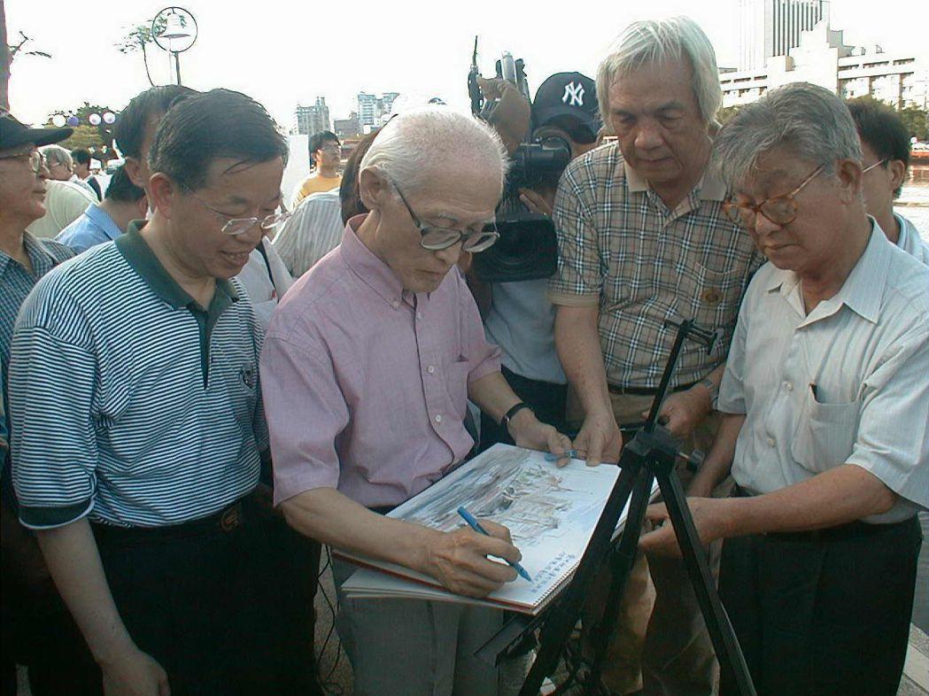 2001年,余光中(左二)在愛河水彩畫上寫下詠讚愛河的詩句;左一為時任高雄市長的...