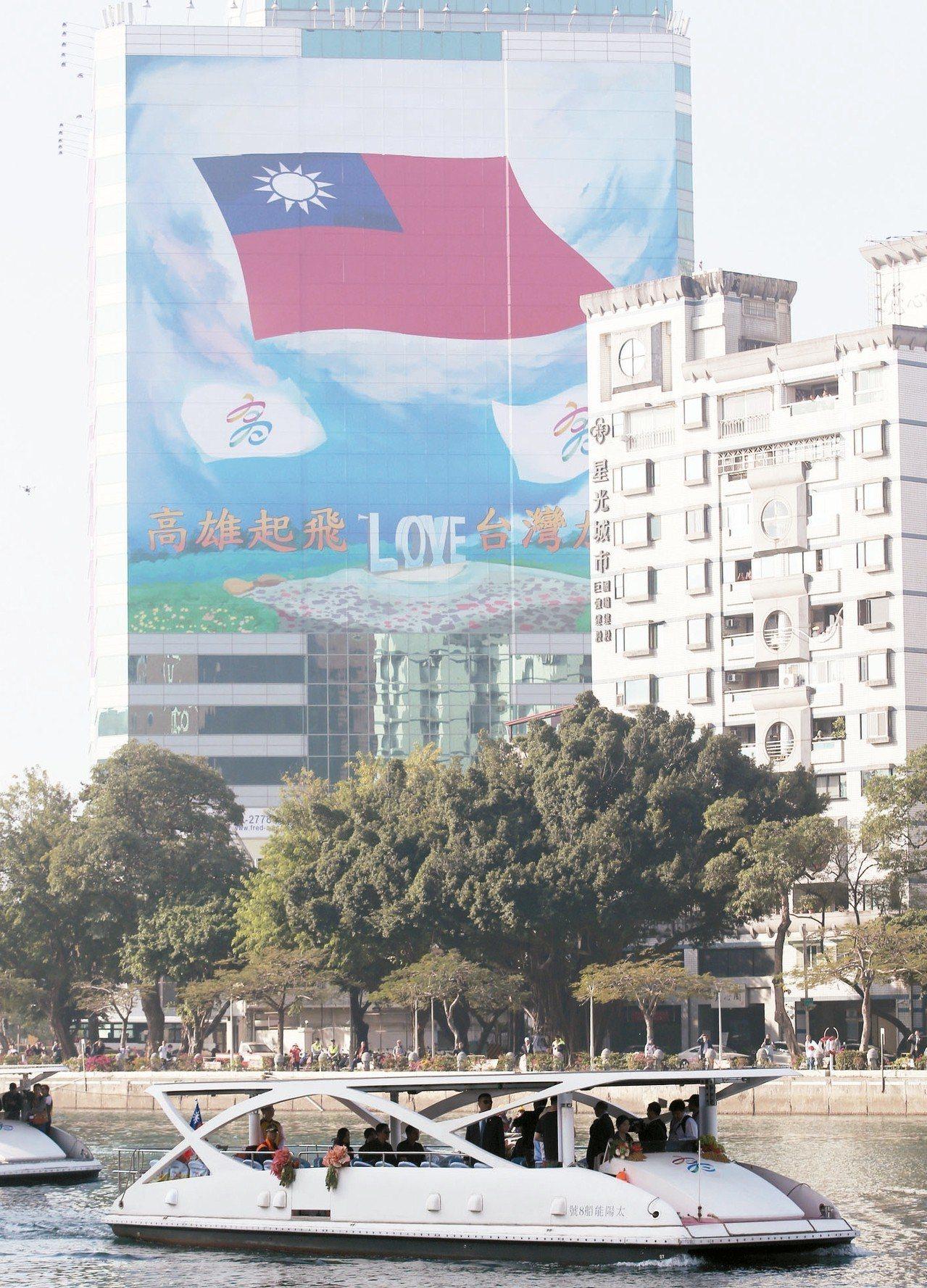 高雄市長就職典禮在愛河舉行,新任市長韓國瑜搭船進場向民眾揮手。河畔高樓有民眾掛出...