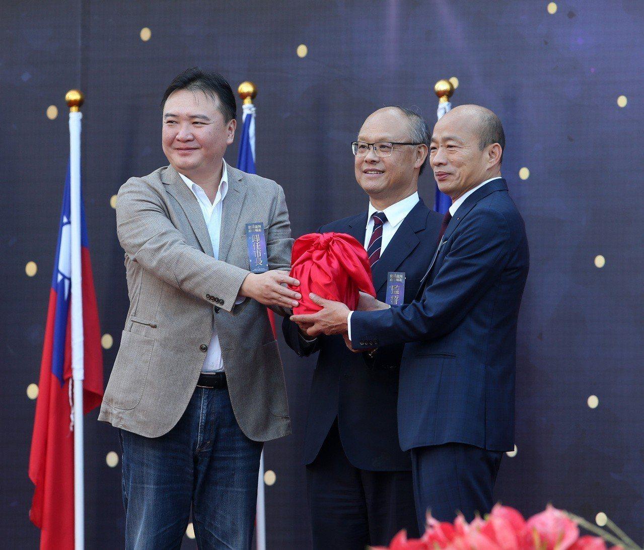 高雄市長就職典禮在愛河舉行,新任市長韓國瑜(右)與代理市長許立明(左)交接印信。...