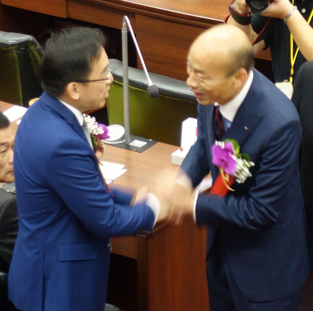 高雄市長韓國瑜(右)今天在高雄市議會和新科議員、前總統陳水扁的兒子陳致中握手。記...