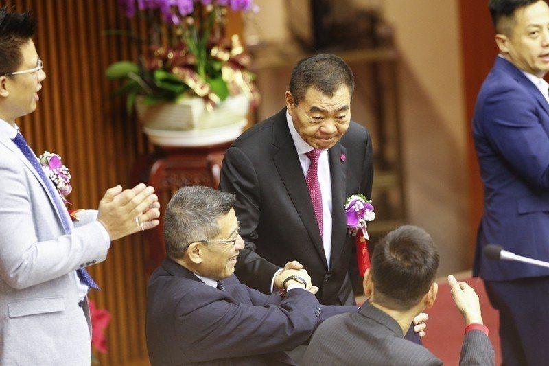 台北市議會25日舉行議長選舉,陳錦祥(中)以第一高票當選議長後,一一跟議員握手感...