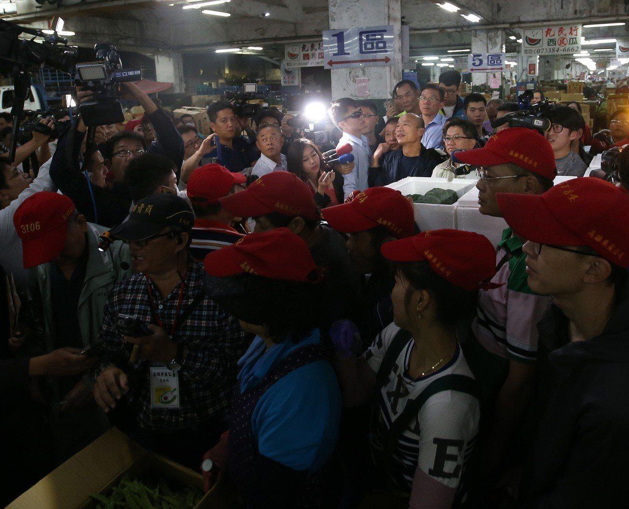 高雄市長韓國瑜(後右)清晨三點起床,視察高雄十全果菜市場。韓國瑜特別駐足,聽拍賣...