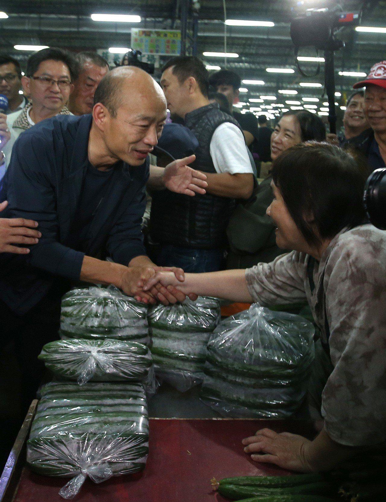高雄市長韓國瑜(左)清晨三點起床,視察高雄十全果菜市場,與攤商交流聽取意見。記者...