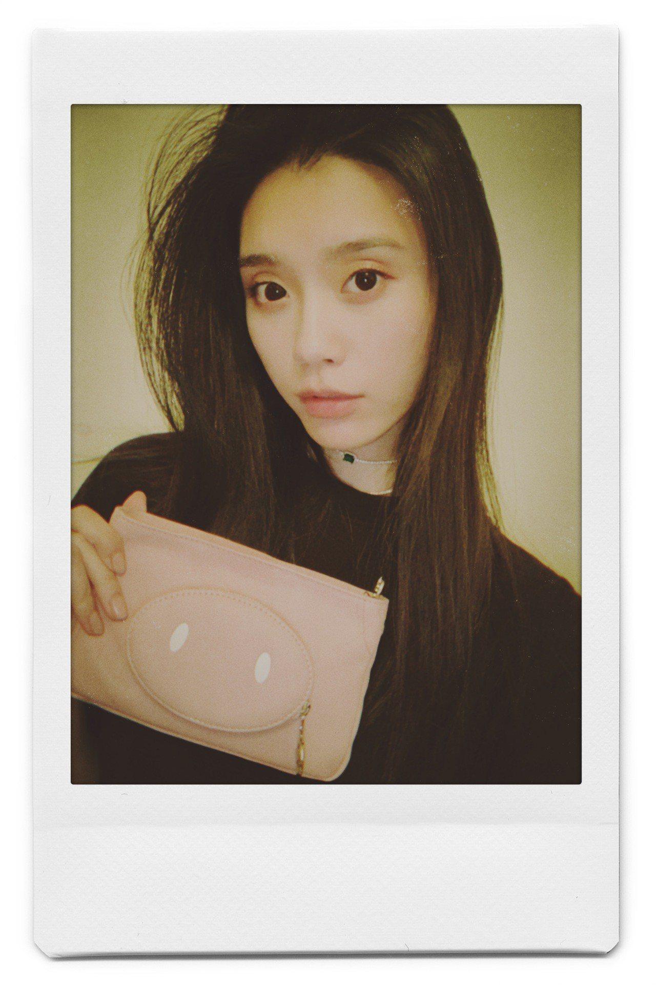 奚夢瑤以藕粉色手拿包拍出個性美。圖/LONGCHAMP提供數位用圖