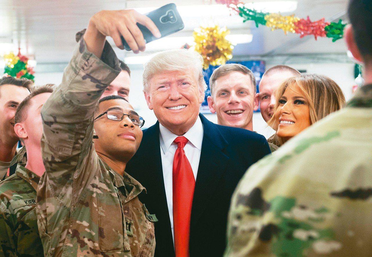 美國總統川普(中)和第一夫人梅蘭妮亞(右)廿六日造訪伊拉克,和當地美軍玩自拍。 ...