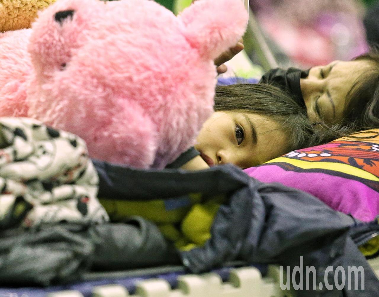 花蓮強震後,家長帶著小孩在收容中心避難,雖有玩偶陪伴,但孩童眼神中仍透露出驚恐。...