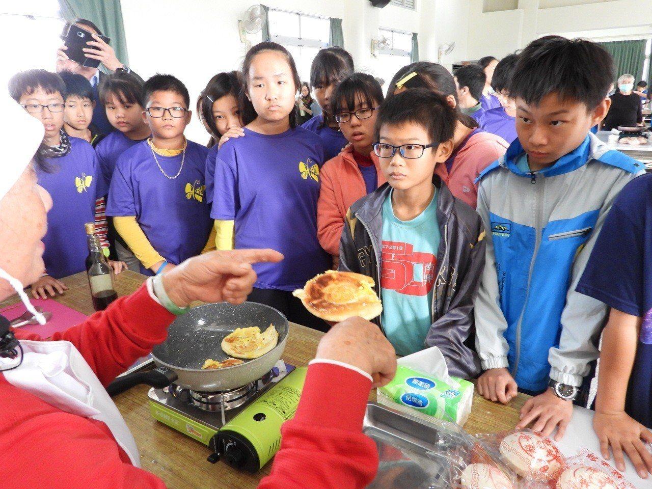 五婆示範教作麻油椪餅,小朋友專心學作。記者周宗禎/攝影