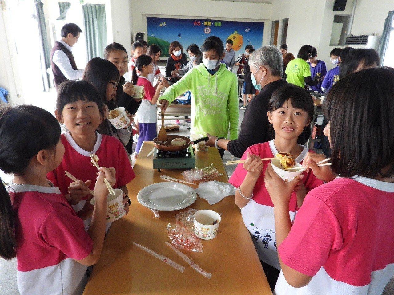 五婆示範教作麻油椪餅,小朋友專心學作,作好品嘗直呼好吃。記者周宗禎/攝影