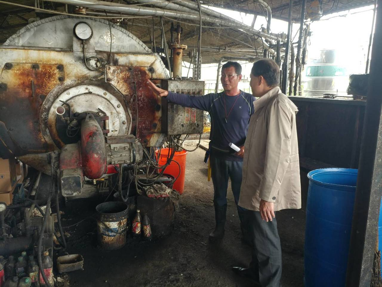 高雄市政府農業局長吳芳銘(右)查看轄內廚餘養豬場。圖/高雄市農業局提供