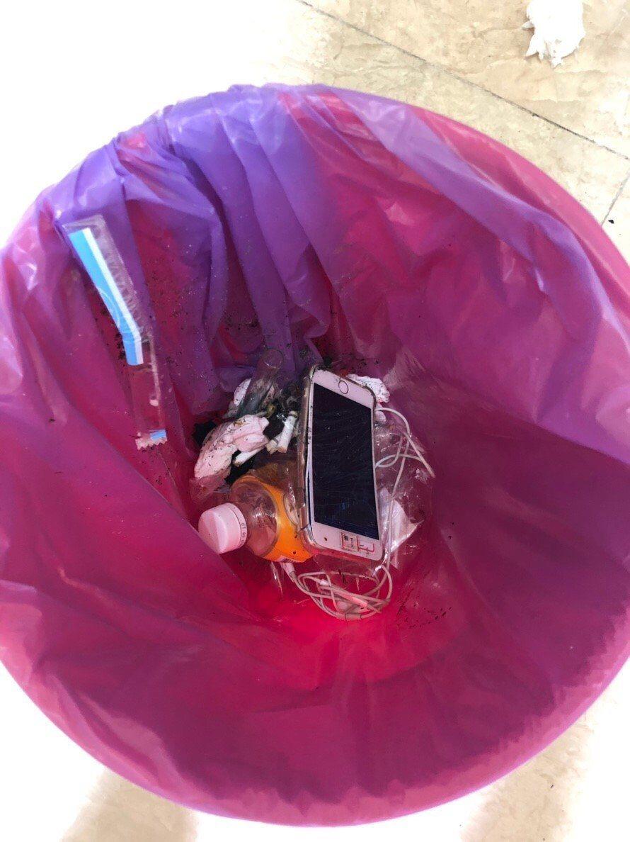 檢調人員突擊詐騙集團的機房,成員心慌把手機等物品丟進垃圾桶。記者何烱榮/翻攝
