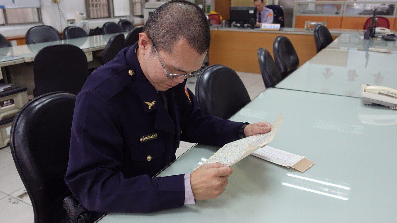 高市鳳山警分局鳳崗所員警李權峰讀著老婦人寫的感謝信。記者劉星君/攝影