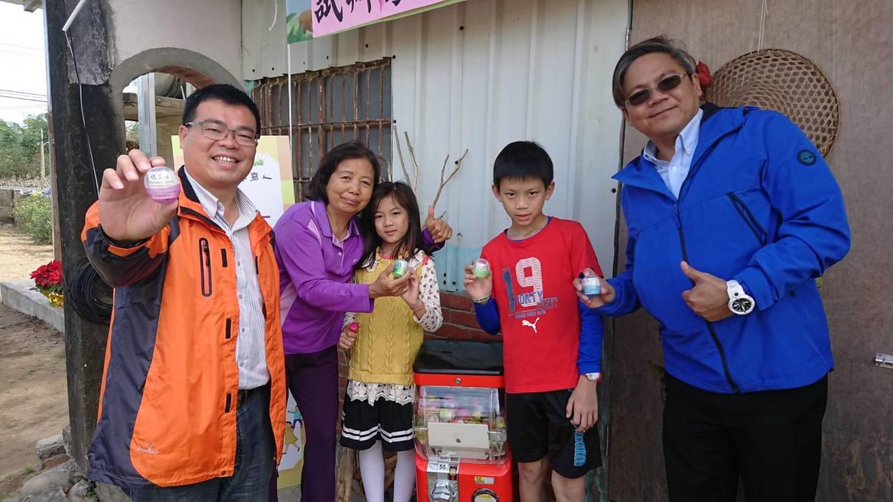 大林鎮長簡志偉(左),與上林社區居民一起投幣玩扭蛋。記者卜敏正/攝影