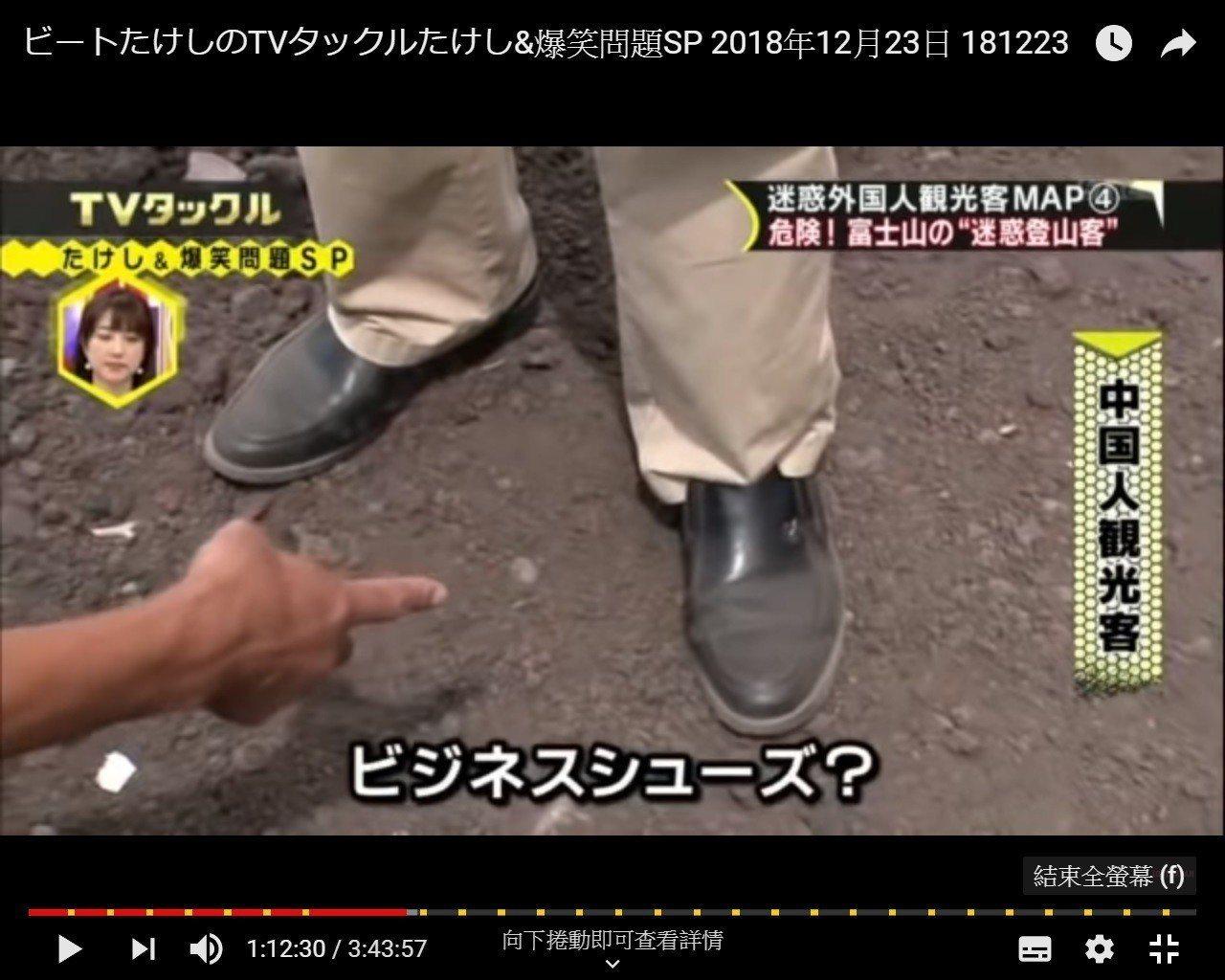 穿著襯衫和皮鞋爬富士山的中國男子。(取自YouTube)