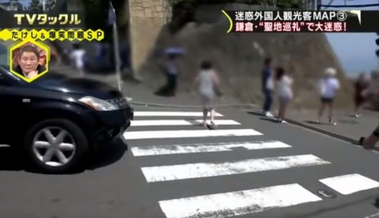 一名女子站在路中間拍照,無視紅燈和準備經過的車輛。(取自YouTube)