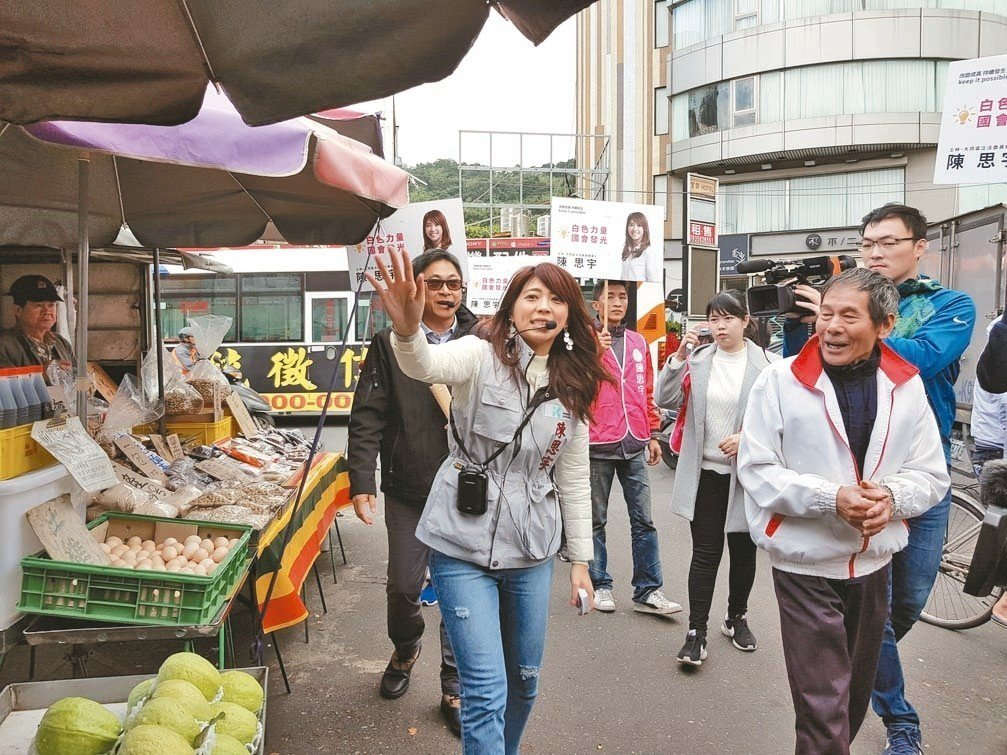 陳思宇(左)昨天上午到士林市場掃街,父親、議員陳建銘(後)陪同在旁。 記者翁浩然...