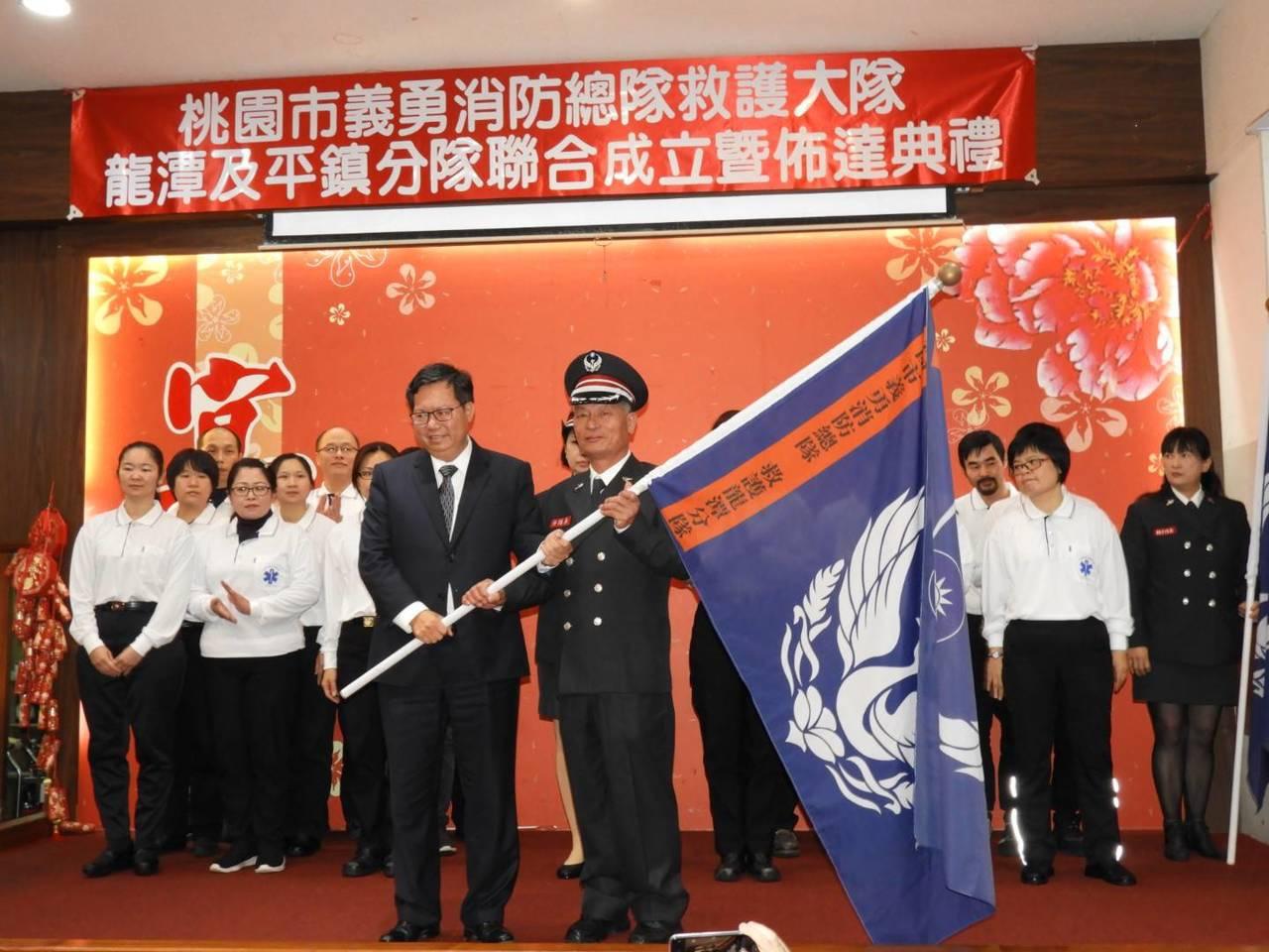 桃園市長鄭文燦(左)到場為平鎮、龍潭分隊授旗。圖/桃園市消防局第四大隊提供