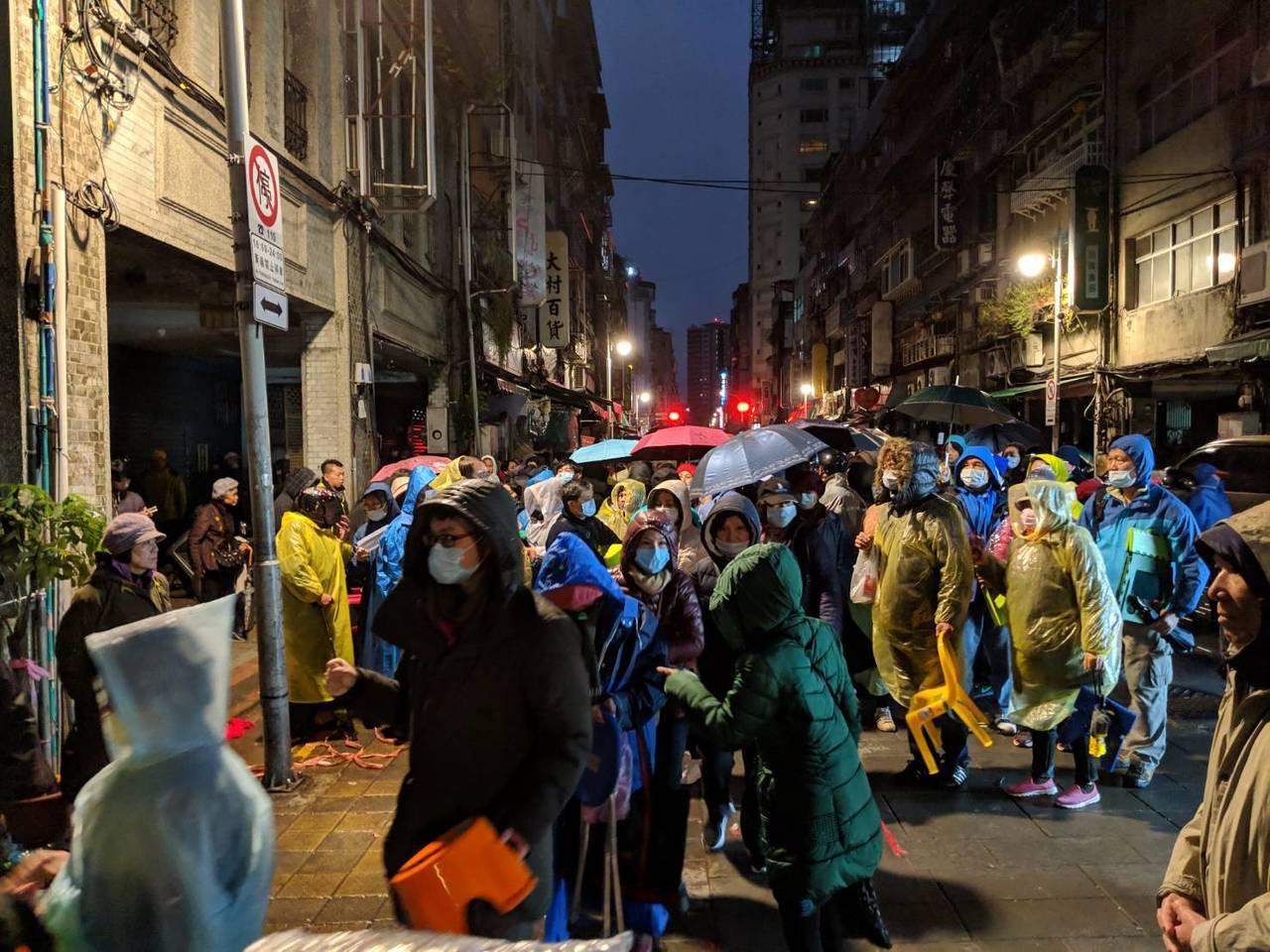 為求來年平安,北市龍山寺每年都出現大批民眾排隊領取點光明燈號碼牌。圖/民眾提供