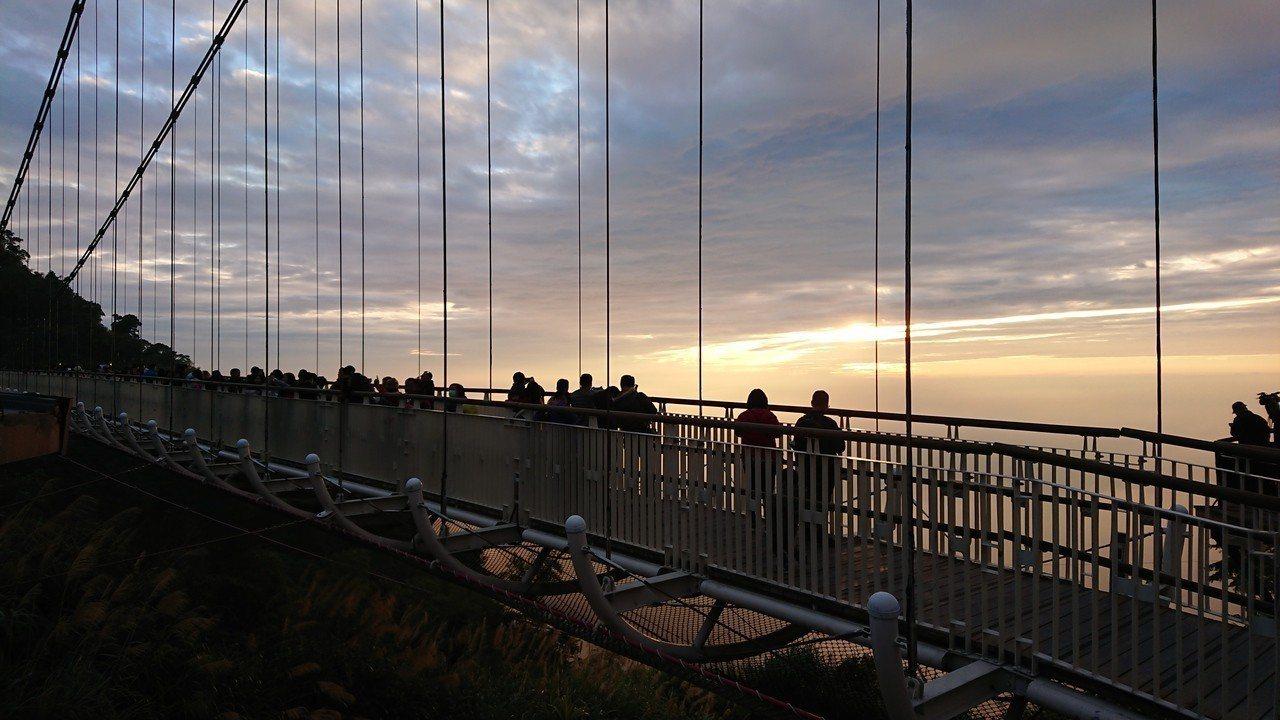 遊客在太平雲梯上歡送、欣賞2018最後夕陽。 記者卜敏正/攝影