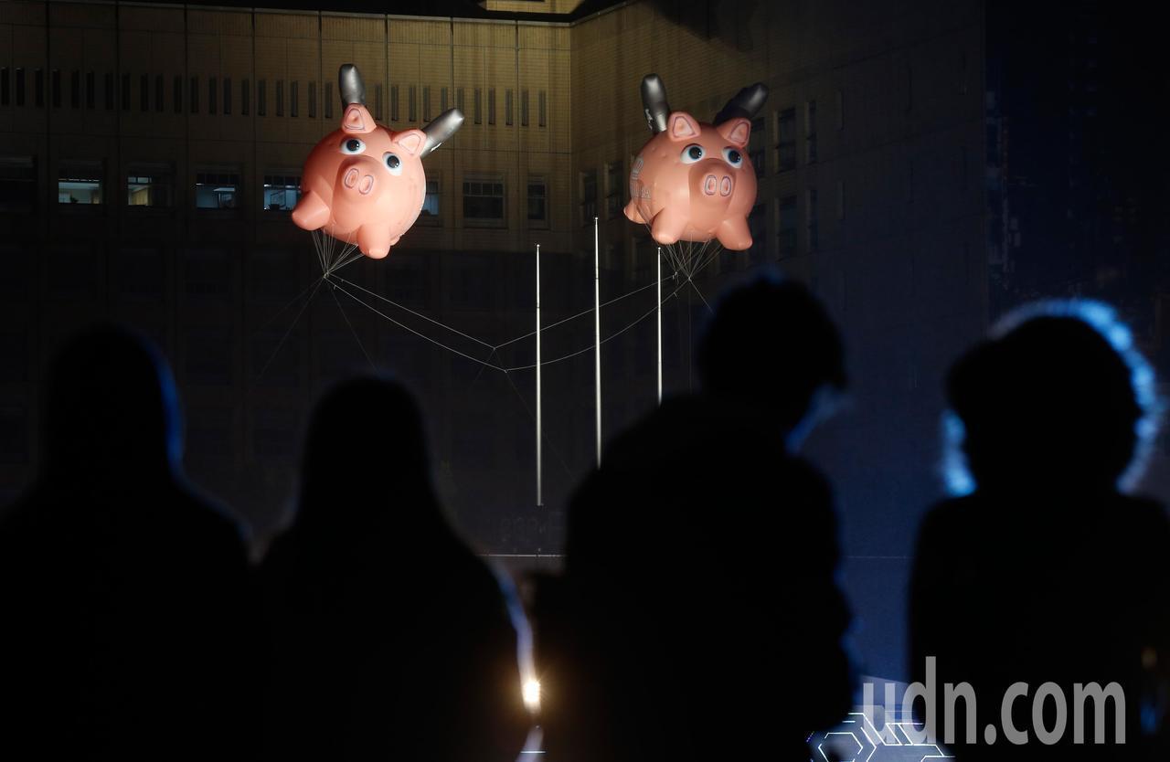 跨年演唱會晚上在台北市府廣場舉行,民眾在高處觀賞演出,市府上方飄著兩著小豬迎豬年...