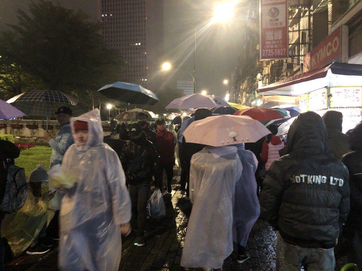 晚間雨勢不斷,但北市府附近仍吸引不少民眾撐傘、穿輕便雨衣排美食。記者陳靖宜/攝影