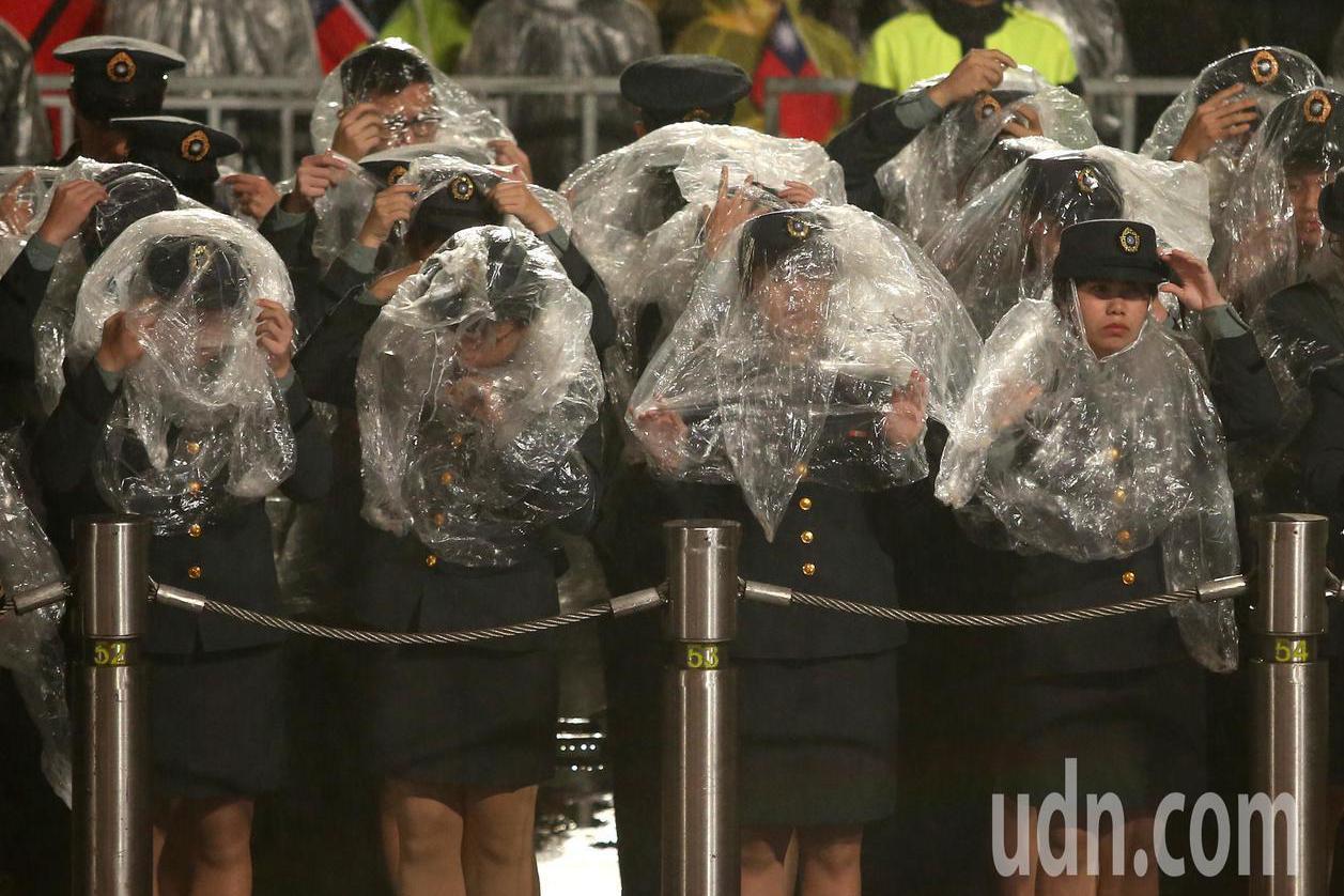 108年元旦升旗典禮清晨在綿綿細雨中舉行,出席的軍校生在場邊穿起雨衣。圖/台北市...