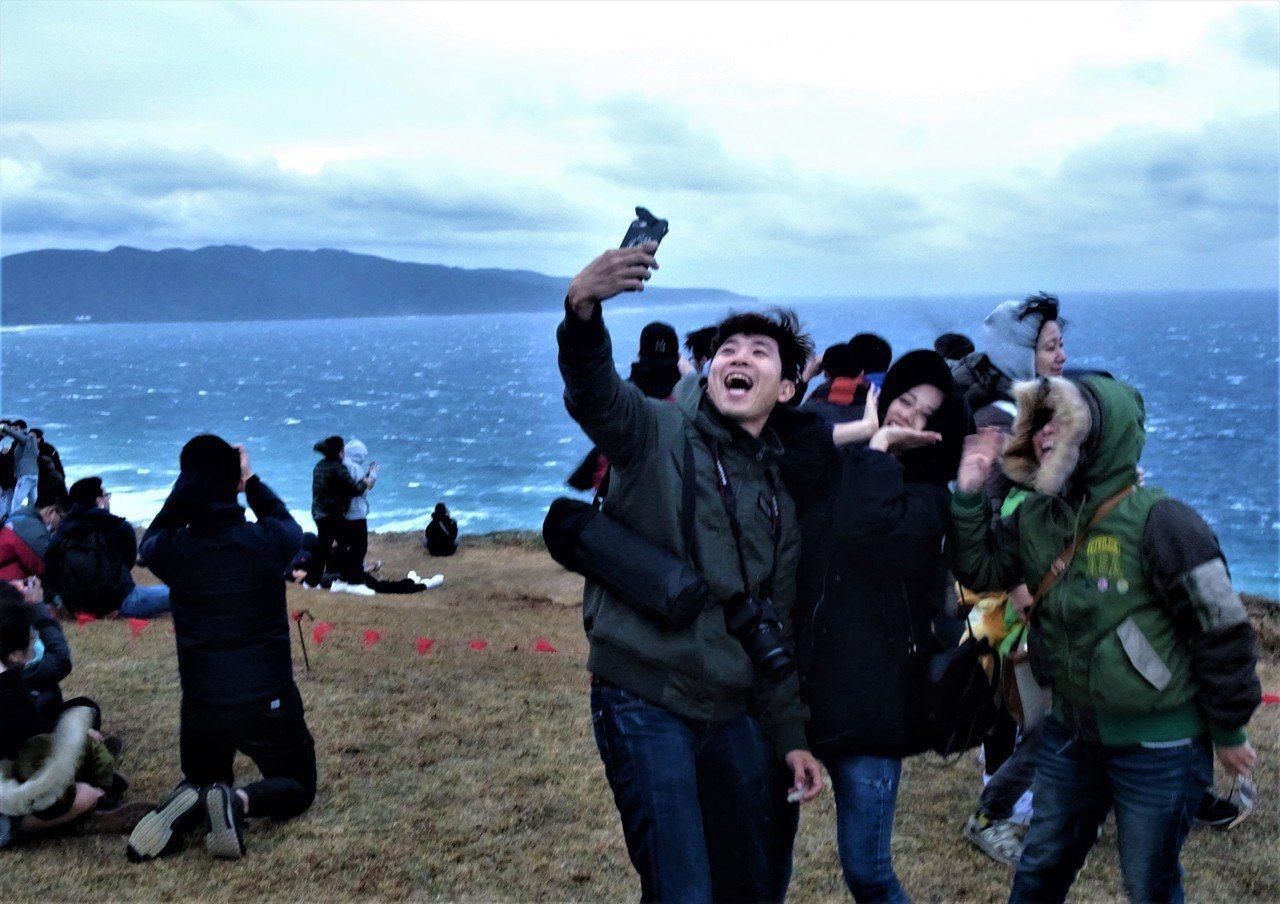 上萬遊客湧入墾丁龍磐草原,冒著超大強風在海邊等候曙光現身,沒看到曙光,還是要拍張...