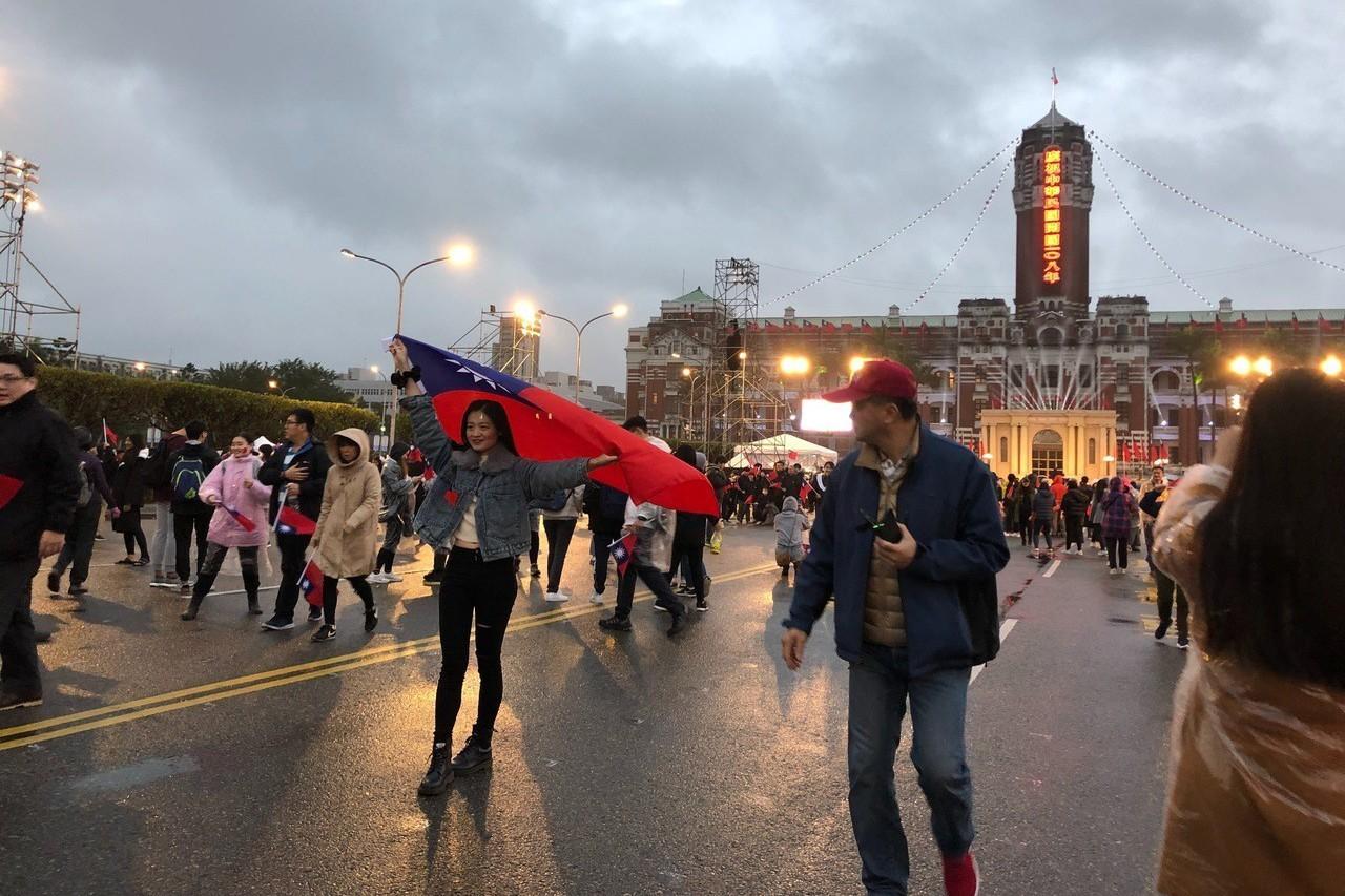 民眾攜帶國旗到總統府前參與升旗典禮,並拍照留念。記者張文馨/攝影