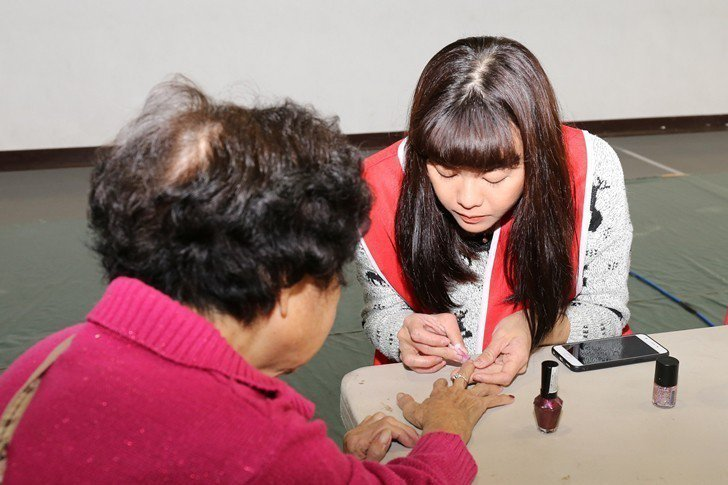 長者們開心體驗時尚系的指甲彩繪服務。 醒吾科大/提供
