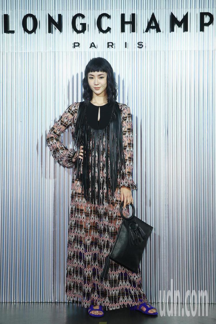 鍾瑶身穿酒紅色A字飄逸連身長裙57,900元、手拿包19,000元、寶藍色羅馬鞋...