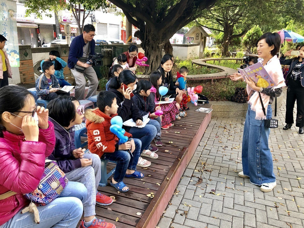 聯聚建設董事長江韋侖的太太阮旭輝,在大樹下為小朋友說故事。記者宋健生/攝影