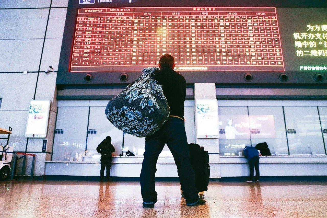 1月6日起,旅客可以通過網路或電話購買除夕(2月4日)的火車票。圖為旅客在鐵路上...