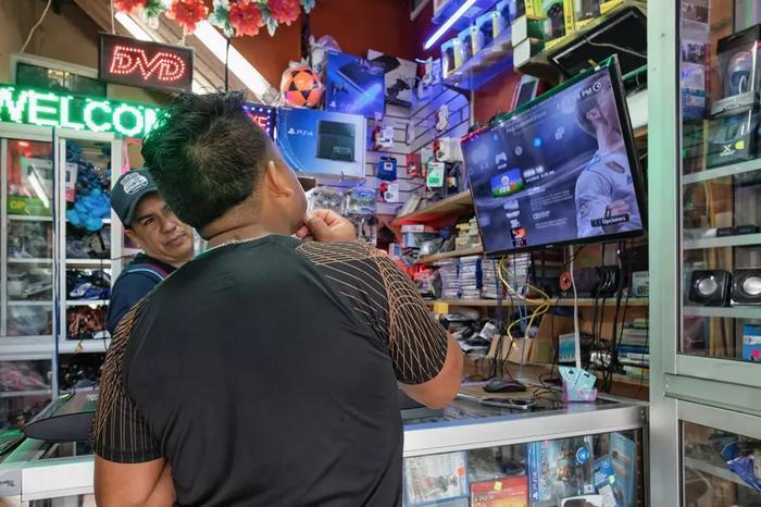 一个典型的厄瓜多電子商店,店主在给Delgado展示裝好的遊戲。