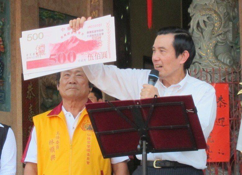 前總統馬英九(右)拿著消費券樣本,表示2008年就是靠它刺激買氣。 圖/聯合報系...