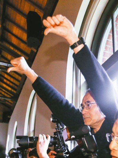 台大上午舉行校長交接典禮,不滿管的台大教授倒豎大拇指抗議。 記者陳柏亨/攝影