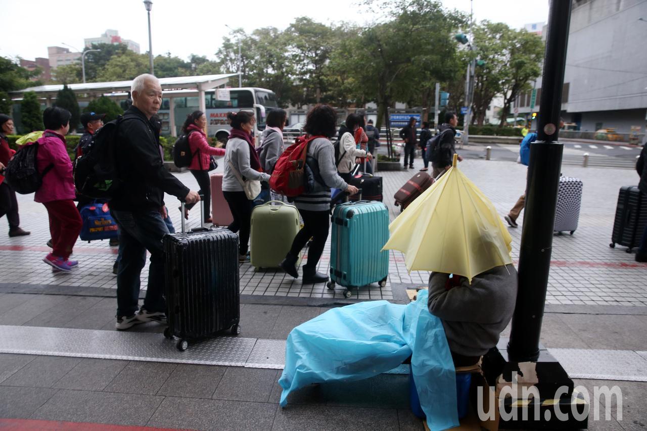 寒冷的台北車站,一群旅客拉著行李箱走過一位遊民旁,遊民席地而坐,撐著一隻傘,用一...