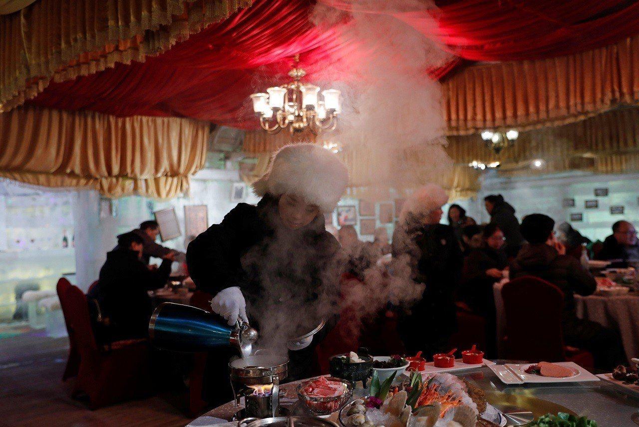 中國黑龍江省哈爾濱香格里拉大酒店「冰宫+冰吧」工作人員正在火鍋注入滾燙高湯。整間...