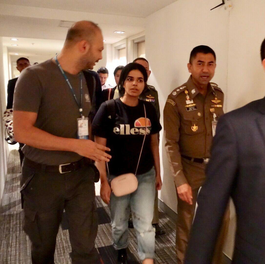 沙烏地阿拉伯少女奎農(中)7日在泰國移民署署長蘇拉切(右)陪同下,離開曼谷機場旅...