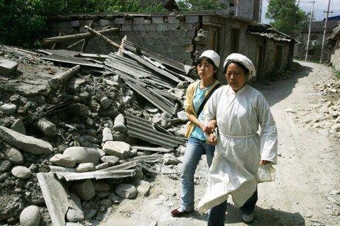 一身孝服的茂縣母親,剛剛埋葬了汶川大地震發生時進屋救災而殉職的鄉干部丈夫,又把受...