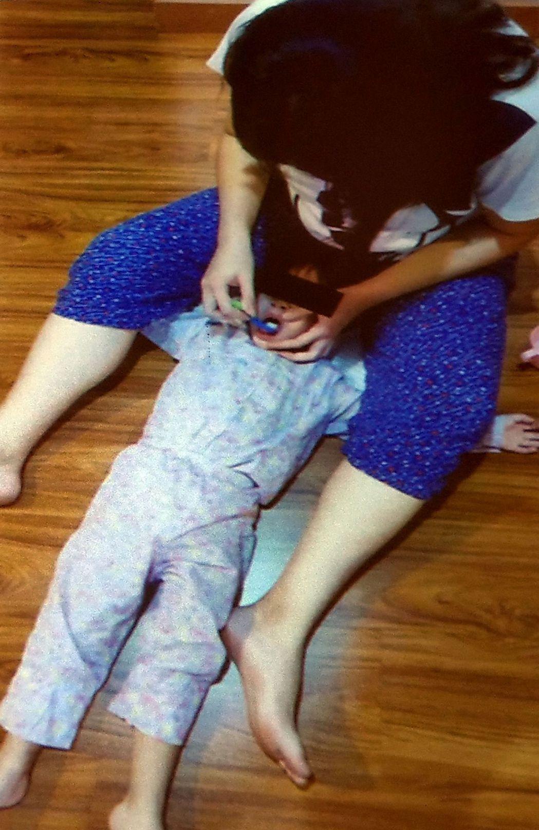 醫師洪仲銳說明,幫3歲以下孩子刷牙,家長可用腳固定孩子手,確實幫孩子刷牙。圖/洪...