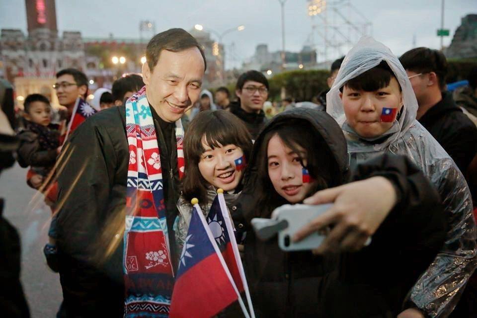 朱立倫在卸下公職後,到總統府前參加升旗典禮,與青年朋友合照。 圖/截取自朱立倫...