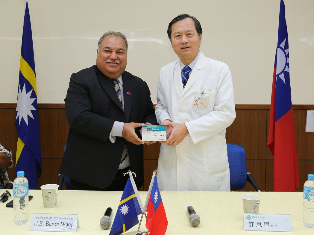 臺中榮民總醫院院長許惠恒(右)致贈登革熱快速篩檢試劑。 臺中榮總/提供。
