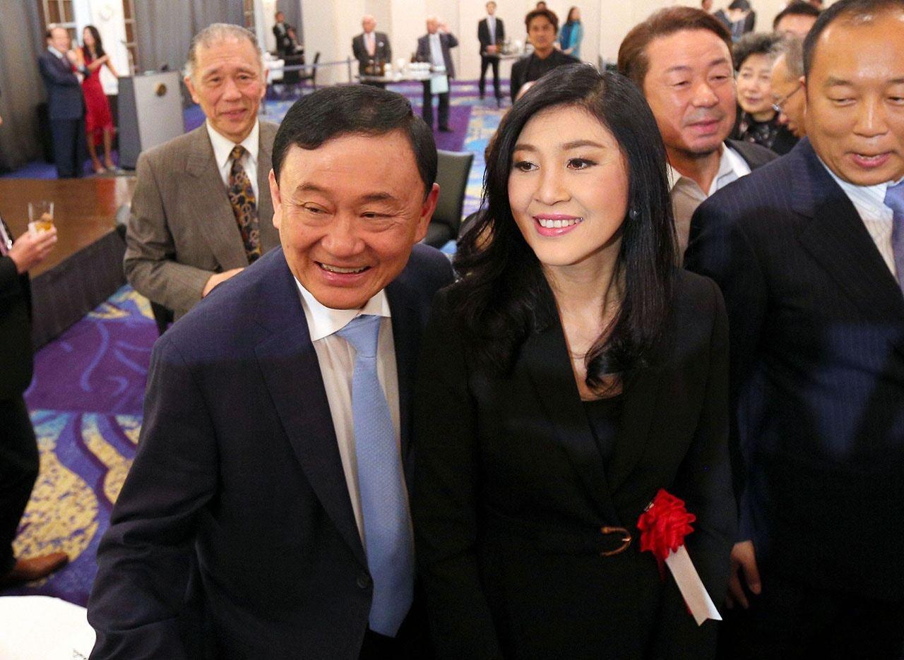 英祿(右)在2011至2014年擔任泰國總理,之後因政變被趕下台,2017年流亡...
